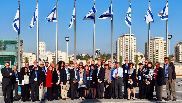 URJ board mission participants in front of Israeli flags on flag polls