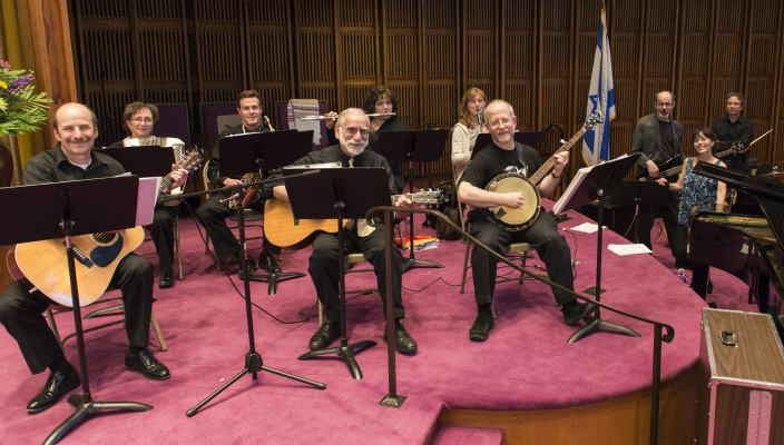 Baby boomers involved in a synagogue band on the bimah
