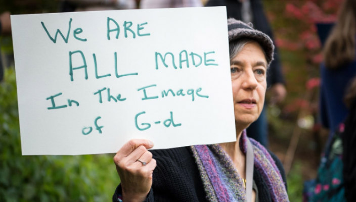 Woman holding a handwritten sign that says We Are All Made in the Image of God