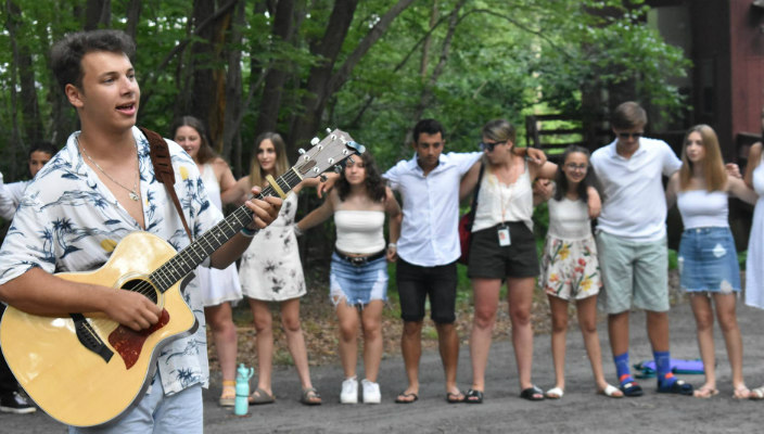 Songleader strumming a guitar in the foreground with people gathered in a circle around him in the background
