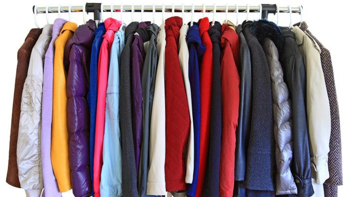 Assorted coats hanging on hangers on a coat rack