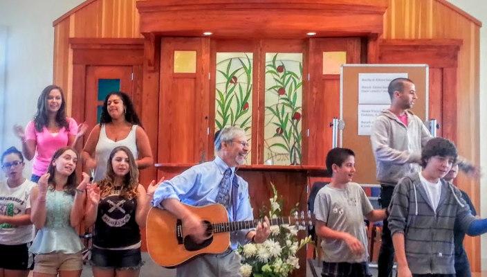 Man playing guitar on bimah surrounding by teens singing along