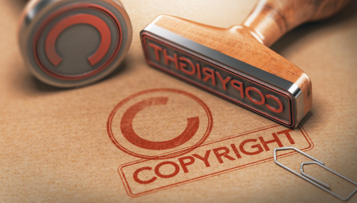 Two copyright stamps and their imprints in red ink on brown paper