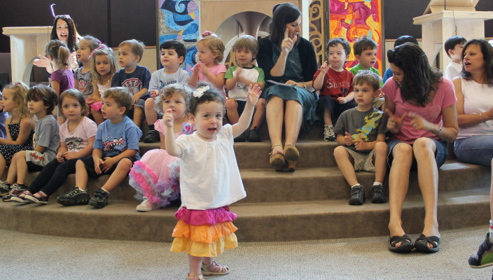 Preschoolers and a few adults sitting on the steps of a bimah