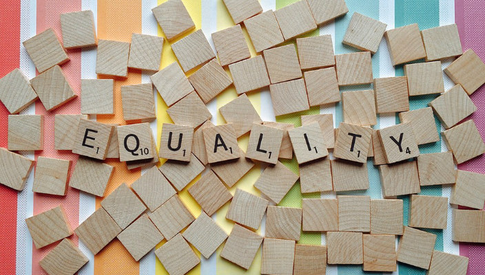 The word EQUALITY spelled out in wooden Scrabbble tiles sitting atop a rainbow printed surface