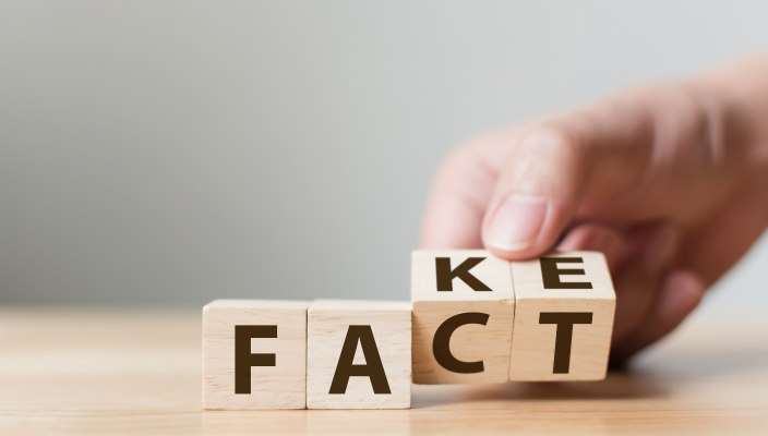 A hand changing the last two letters of the work FAKE to the word FACT