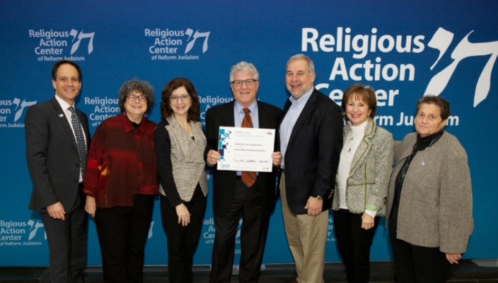 Past Fain Award winners posing in front of a Religious Action Center banner with their award