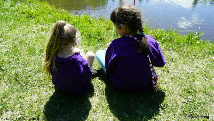 Two girls on the bank of a pond