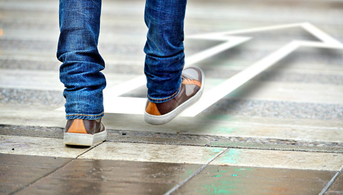 Tile floor with a pair of jean-clad legs and sneaker-clad feet taking a step forward in the direction of an arrow that is a few inches off the floor
