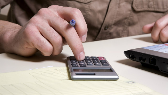 Person with a pen in hand using a calculator