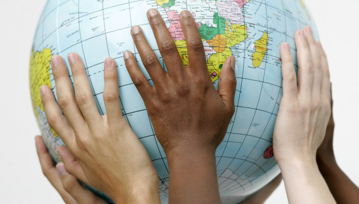 Hands of people of different races holding up a globe