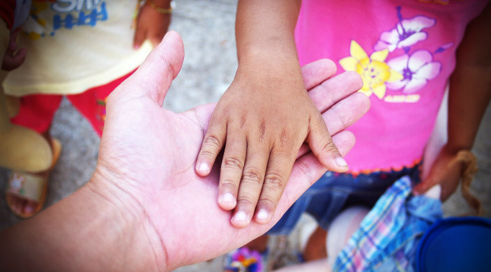Childrens hands touching one adult hand