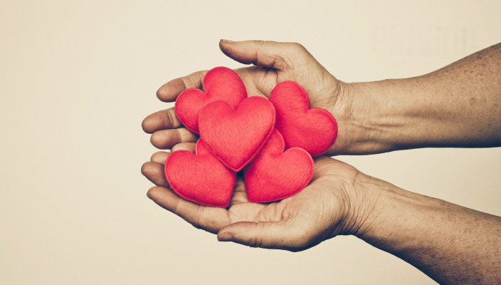 Pair of hands, palms upward with red, heart-shaped objects in the palms