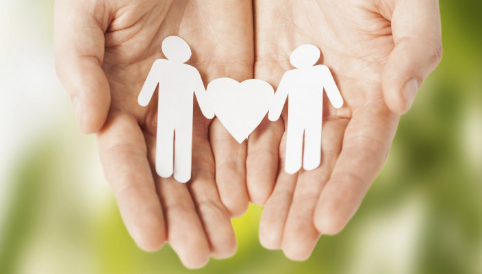 Cupped hands holding a paper cutout of two male shaped stick figures with a heart between them