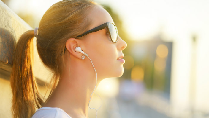 Young woman in profile, wearing sunglasses and earbuds