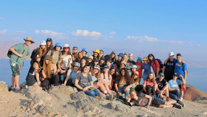 Group of smiling URJ Heller High students standing on a sandy hill in Israel