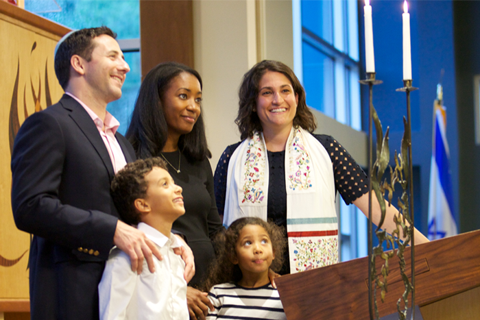 Family and cantor lighting candles in a synagogue
