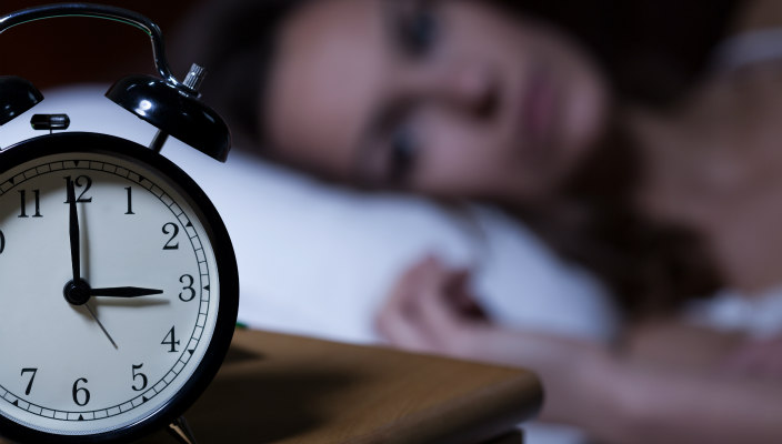 Alarm clock on dresser; woman awake in bed in the middle of the night