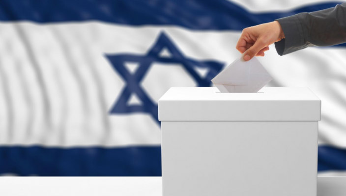 Hand dropping a ballot into a ballot box in front of the Israel flag