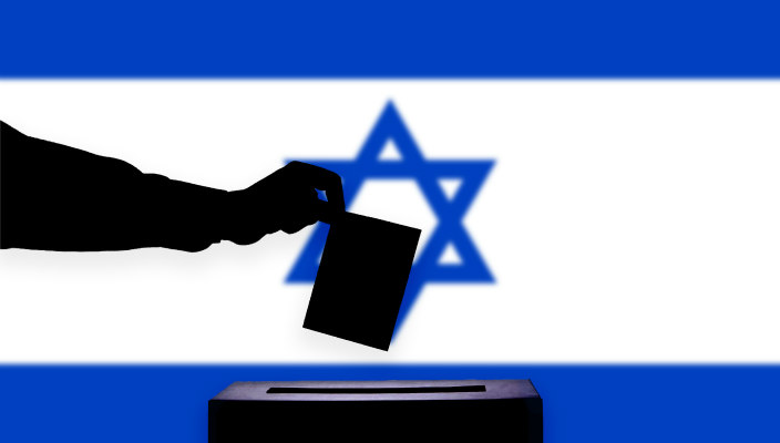 Silhouette of a hand dropping a ballot into a ballot box in front of an Israeli flag