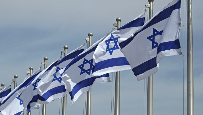 Row of Israeli flags on flagpoles, blowing in the breeze