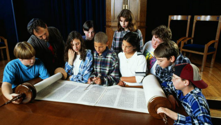 Young teens gathered around the bimah as they look at an open Torah scroll
