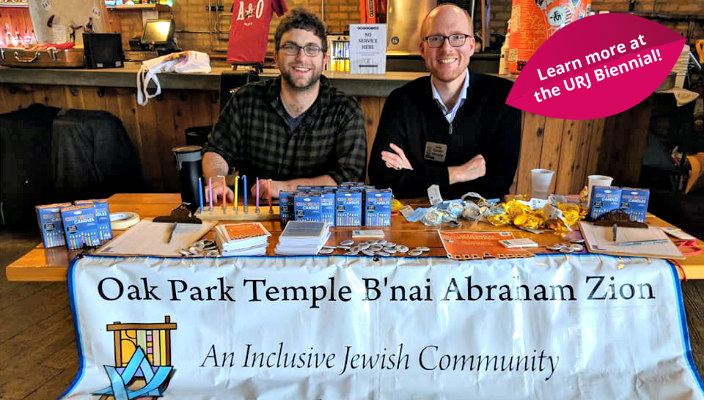 Rabbi Daniel Kirzane and another man sitting at a table with a sign that reads Oak Park Temple Bnai Abraham Zion an Inclusive Jewish Community