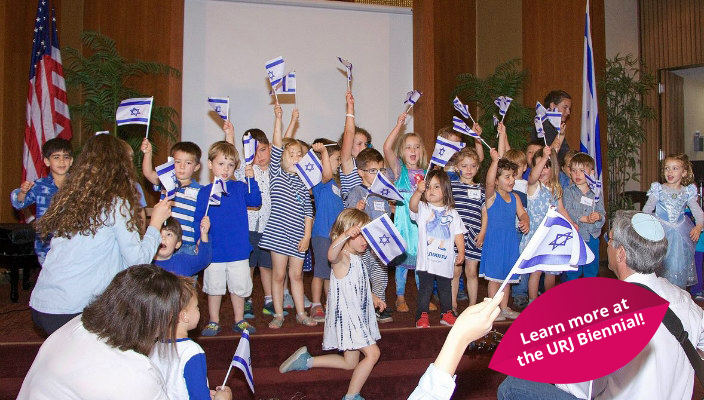 Young children waving Israeli flags on the stage in a synagogue social hall