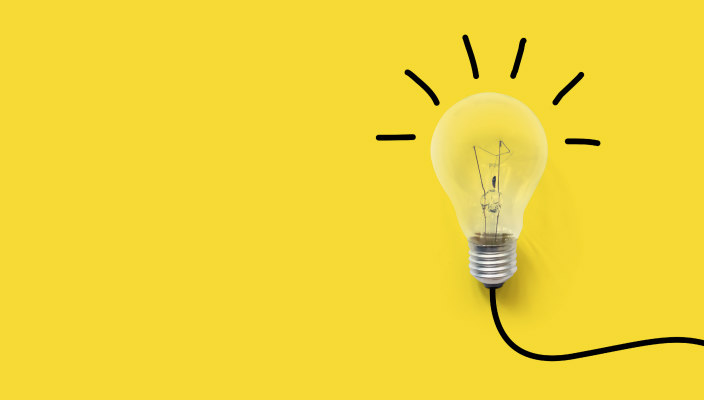 Bright lightbulb against a yellow background