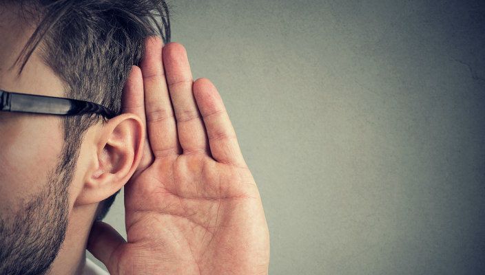 Closeup of a man with a hand to his ear as if listening