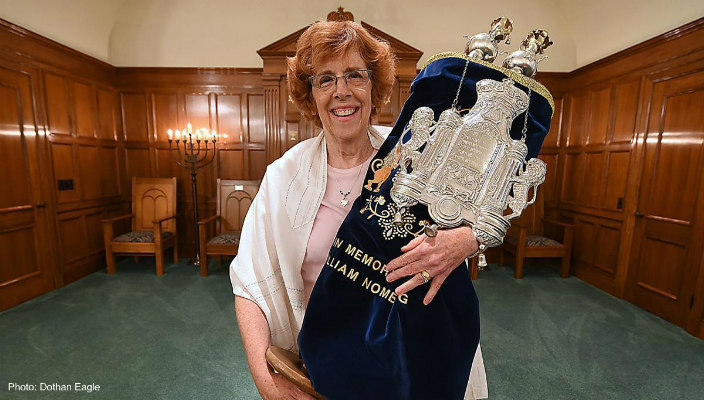 The author holding a Torah scroll on the bimah of Temple Emanu-El in Dothan, Alabama