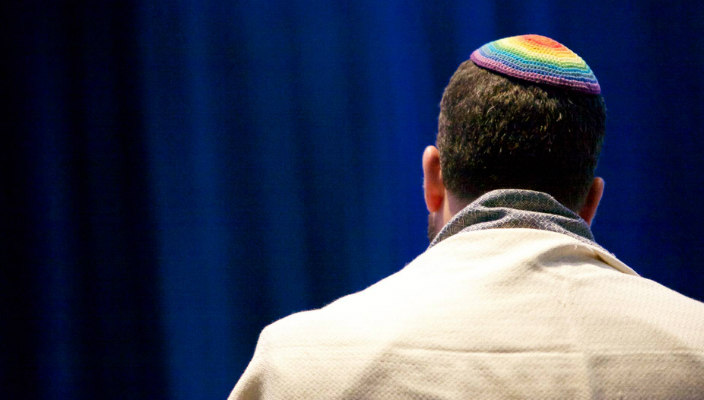 Back of a mans head wearing a rainbow kippah in front of a blue curtain background