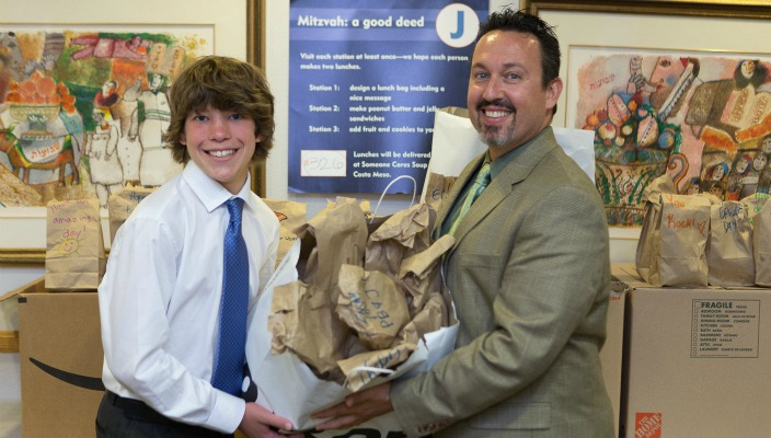 Bar mitzvah boy and rabbi holding a bag full of lunches
