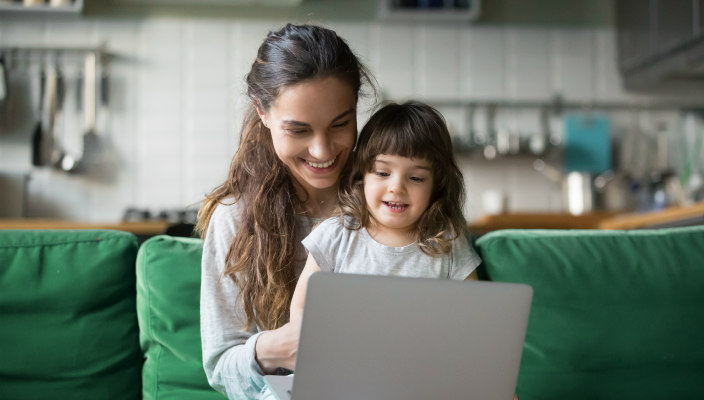 Mom holding daughter on her lap while they look at a laptop from the sofa
