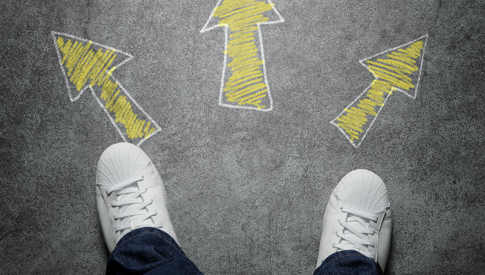 Pair of feet in white sneakers and blue pants seen from above, with three chalk-drawn arrows in front: one pointing left, one pointing right, and one pointing straight ahead