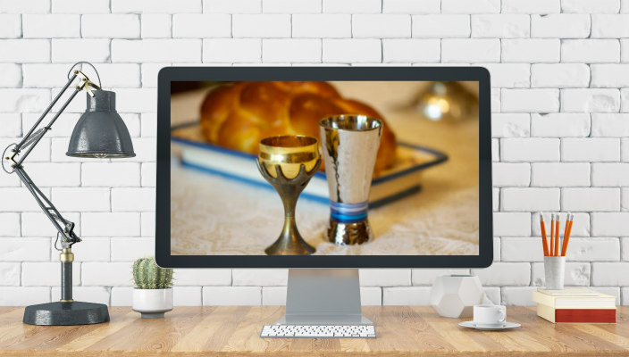 Home office setup with a Shabbat scene displayed on screen