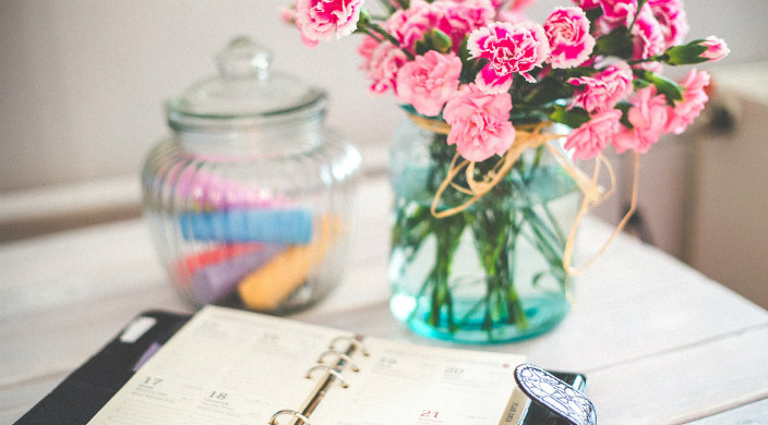 Desk with pink flowers and an open planner set on top of it