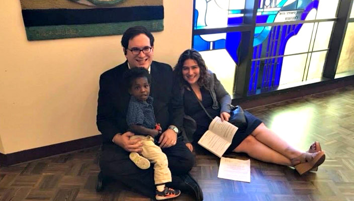 Smiling white couple and their Black son sitting in a synagogue with stained glass behind them