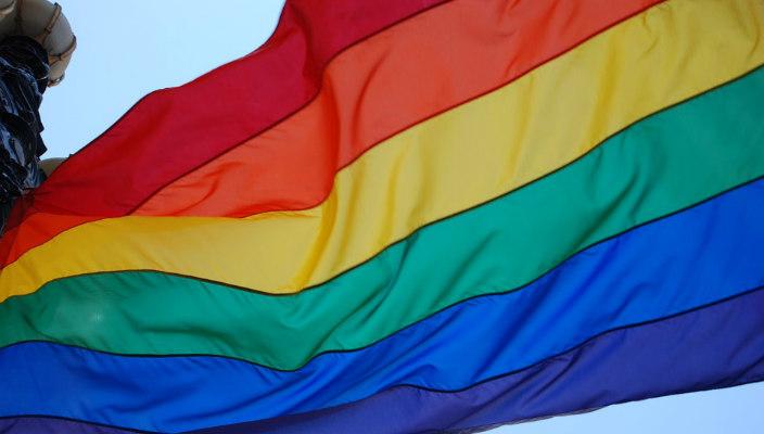 Rainbow Pride flag against a blue sky