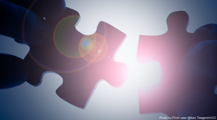 Two puzzle pieces being held in front of bright sunlight