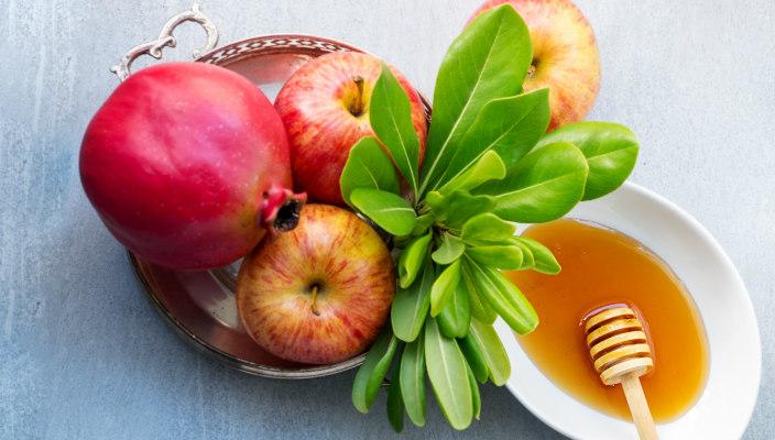 Rosh HaShanah flatlay with honey and pomegranates and apples