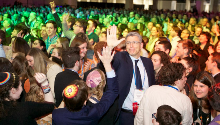 Rabbi Rick Jacobs dancing in the middle of a large crowd at Biennial