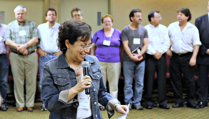 Woman laughing while holding a microphone and speaking in front of a small group