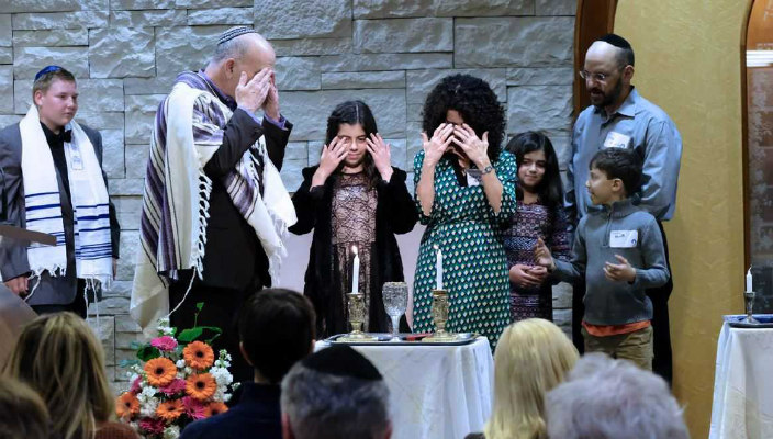 Group of people lighting Shabbat candles at a congregational Shabbat dinner