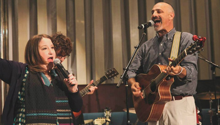 Man and woman playing guitars and singing while leading worship services