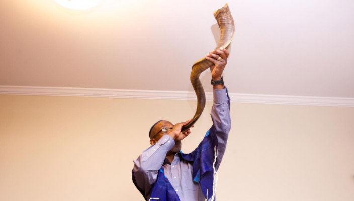 Man blowing a shofar high into the air in front of a white background
