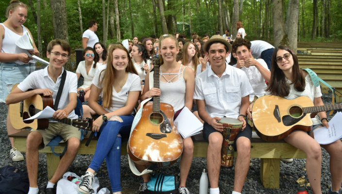 Group of songleaders sitting outdoors at a summer camp holding guitars and wearing all white as if on Shabbat