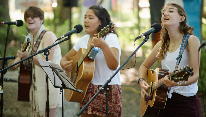 Three young people playing guitars at a summer camp worship service