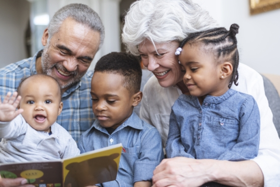 Grandparents reading to three young children