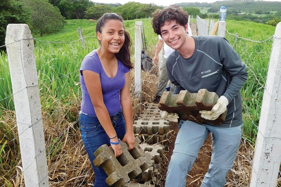 Two Mitzvah Corps participants working in a field and smiling